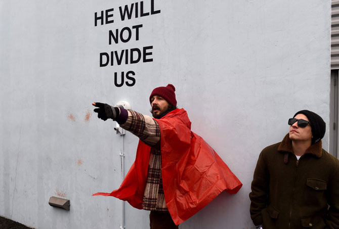 """US actor Shia LaBeouf(L) during his """"He Will Not Divide Us"""" livestream outside the Museum of the Moving Image in Astoria, in the Queens borough of New York January 24, 2017 as a protest against President Donald Trump. LaBeouf has installed a camera at the Museum of the Moving Image in New York that will run a continuous live stream for the duration of Trump's presidency. LaBeouf is inviting the public to participate in the project by saying the phrase, """"He will not divide us,"""" into the camera. Pic/AFP"""